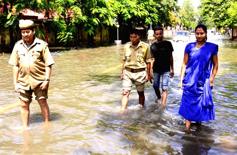 People wade through a waterlogged road in Sivasagar on July 2, 2014.