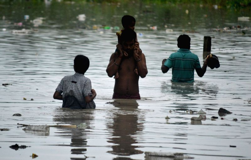 People wade through flooded in Alipurduar district of West Bengal on July 22, 2016.