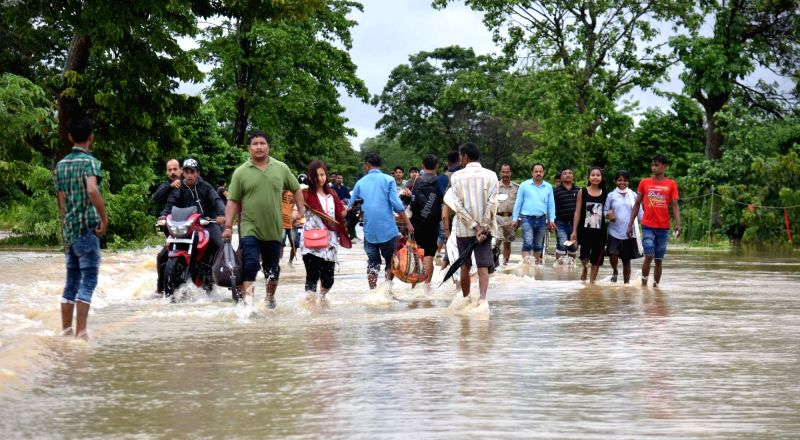 People wade through flooded National Highway-37 at Bokakhat sub-division in Golaghat district of Assam on June 13, 2018.