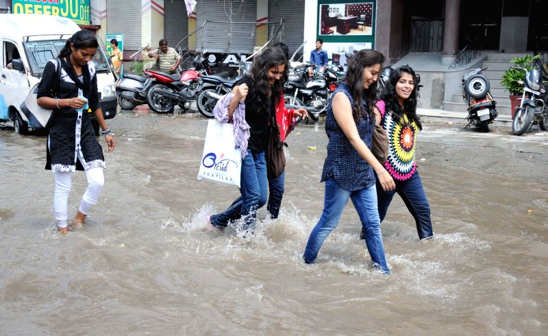 People wade through flooded roads of Amritsar after heavy rains on August 1, 2014.