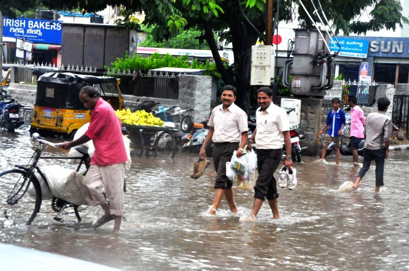 People wade through flooded streets of Secunderabad on Aug 26, 2014.