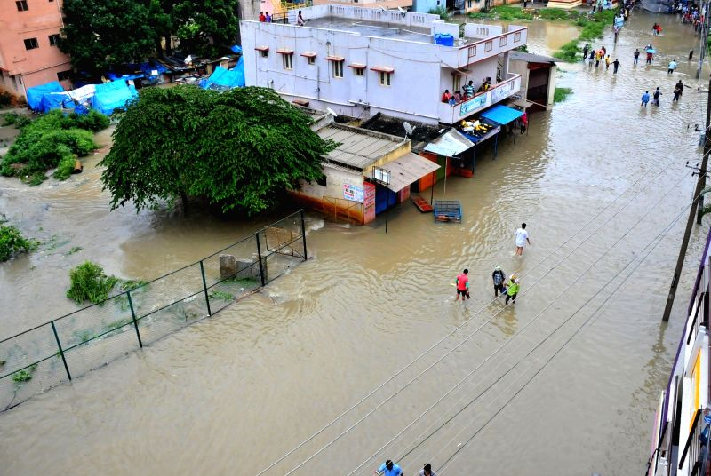 People wade through flooded streets of Bengaluru after heavy rains in on July 29, 2016.