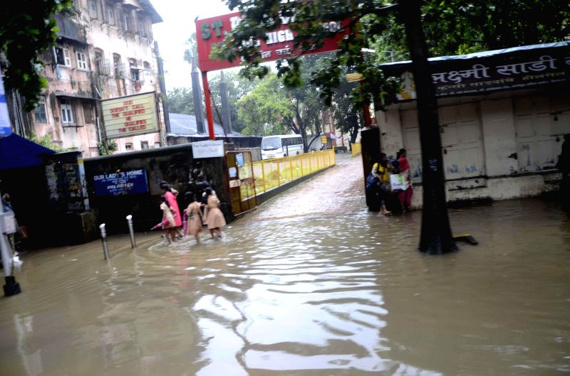 People wade through flooded streets of Mumbai after heavy rains on Sept 1, 2014.