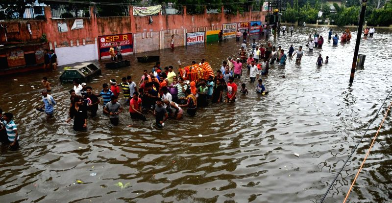 People wade through water logged roads of Patna as they carry a body for cremation on July 29, 2018.