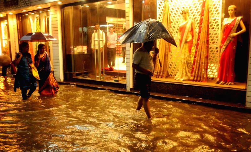 People wade through water-logged streets of Kolkata on July 2, 2014.