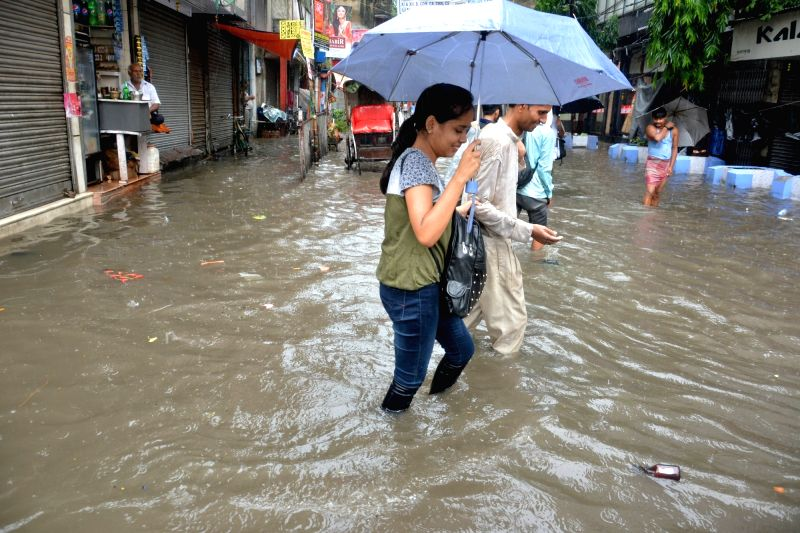 People wade through water logged streets of Kolkata after heavy rains on Aug 5, 2018.