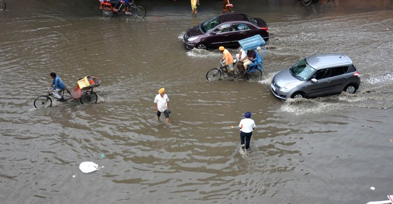 People wade through waterlogged streets of Amritsar after rains on June 25, 2014.