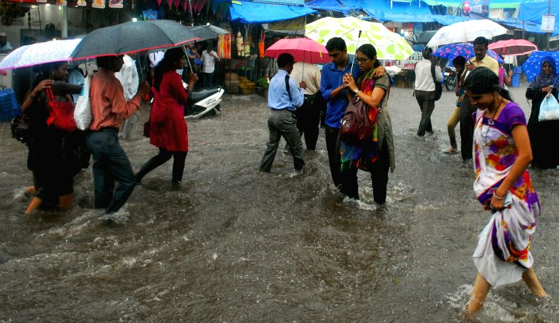 People wade through waterlogged streets of Mumbai after heavy rains in Mumbai on July 2, 2014.