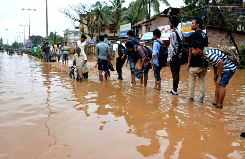 People wade through waterlogged Zoo road after heavy showers in Guwahati on June 27, 2014.