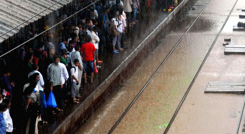People wait for trains to arrive at a platform of Mumbai during heavy rains on July 2, 2014.