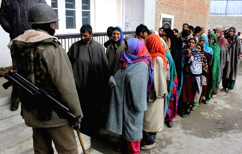 People wait in a queue to cast their votes at a polling station at Harikanwan Village in district Ganderbal of Jammu and Kashmir on Nov. 25, 2014.