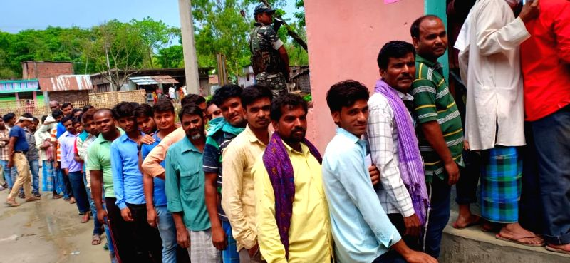 People wait in queues to cast their votes for the third phase of 2019 Lok Sabha elections, at a polling booth in Bihar's Araria, on April 23, 2019. (Photo: IANS)