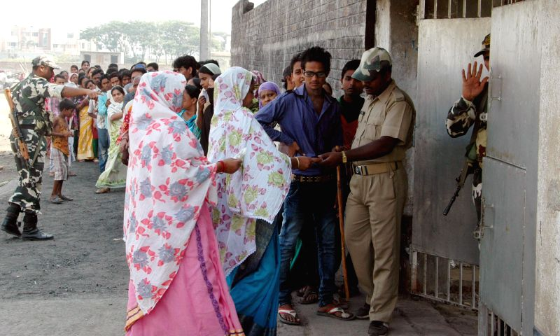 People wait outside a polling booth to cast their votes during the seventh phase of 2014 Lok Sabha Polls in Sreerampur of West Bengal on April 30, 2014.
