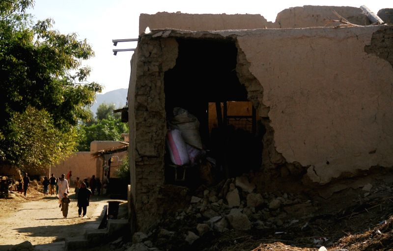 People walk near a destroyed house in Nangarhar province, Afghanistan, Oct. 27, 2015. The death toll of Monday's earthquake in Afghanistan has risen to 115 while ...