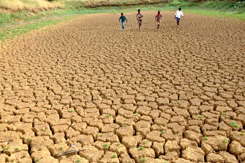 People walk on a piece of parched land on a hot day in Ranchi, on May 20, 2016.