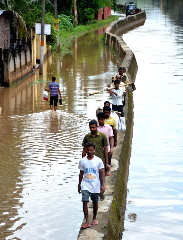 People walk on a wall as roads get flooded after heavy showers in Guwahati on Aug 8, 2014.
