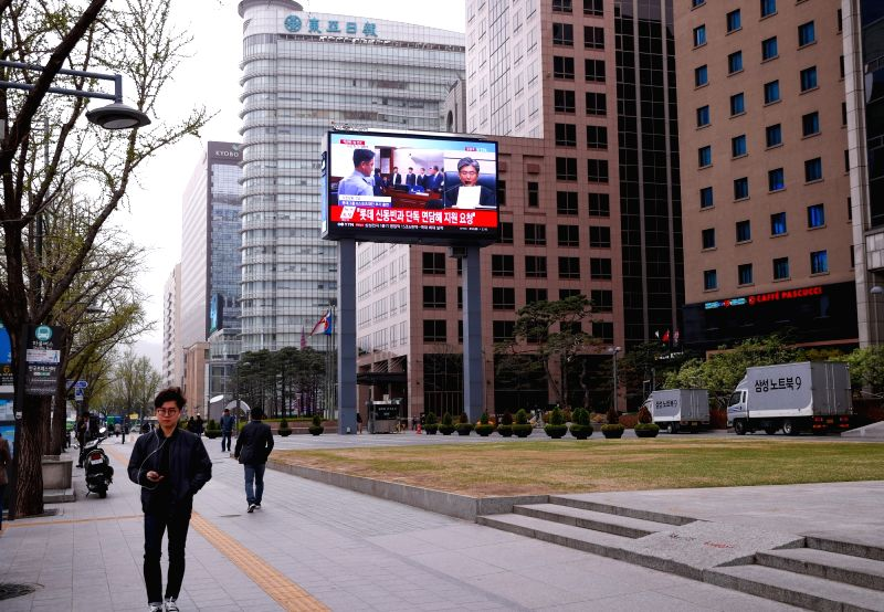:People walk past a giant screen broadcasting the sentence to the impeached President Park Geun-hye in Seoul, South Korea, April 6, 2018. A South Korean court on ...