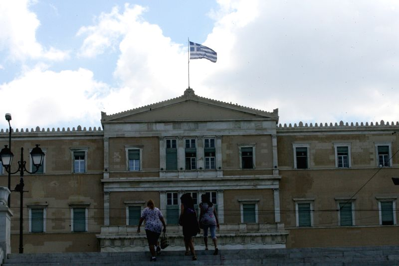 People walk past the Greek Parliament building in Athens, Greece, July 6, 2015. Greek President Prokopis Pavlopoulos convened political leaders for a meeting to ...