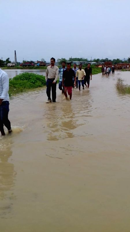 People walk through the water-logged streets after heavy rains flooded many parts of the state, in Agartala on June 13, 2018.