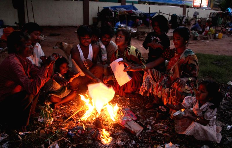 People warm themselves around a fire in Goa on Jan 13, 2015.