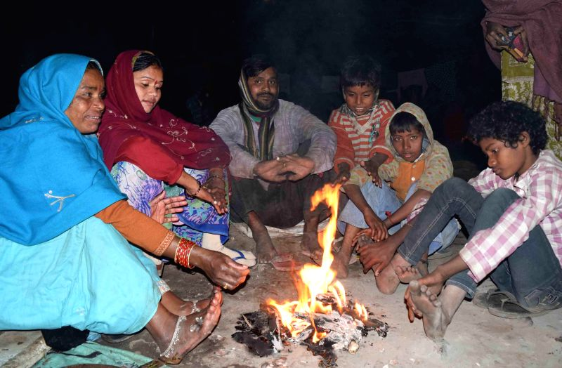 People warm themselves around a fire in Patna, on Dec 28, 2014.