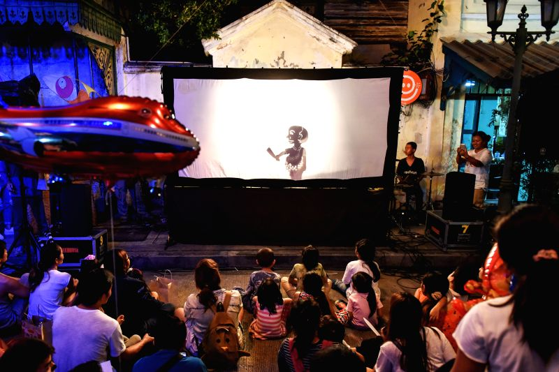 People watch a traditional Thai shadow play during the Sam Phraeng Facestreet Festival in Phra Nakhon District of downtown Bangkok, Thailand, Nov. 22, 2015. The Sam ...