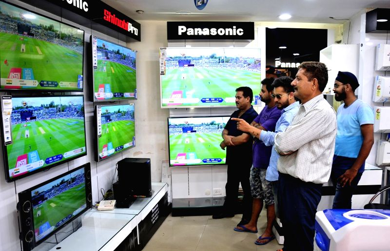 People watch the ICC Champions Trophy match between India and Pakistan at an electronic store in Amritsar, on June 4, 2017. The mach is being played at Edgbaston, Birmingham in UK.