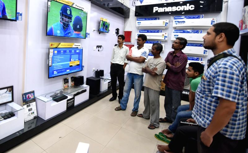 People watch the ICC Champions Trophy match between India and Pakistan at an electronic store in Guwahati, on June 4, 2017. The mach is being played at Edgbaston, Birmingham in UK.