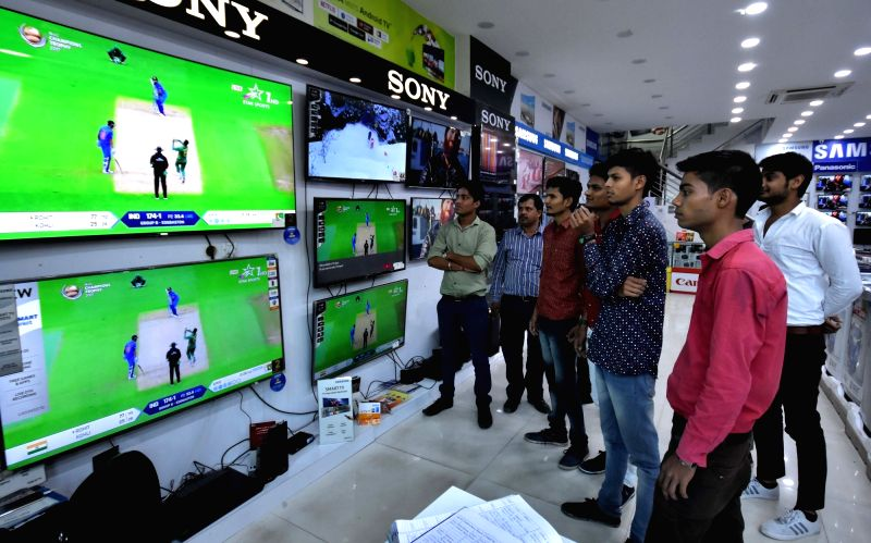 People watch the ICC Champions Trophy match between India and Pakistan at an electronic store in Jaipur, on June 4, 2017. The mach is being played at Edgbaston, Birmingham in UK.