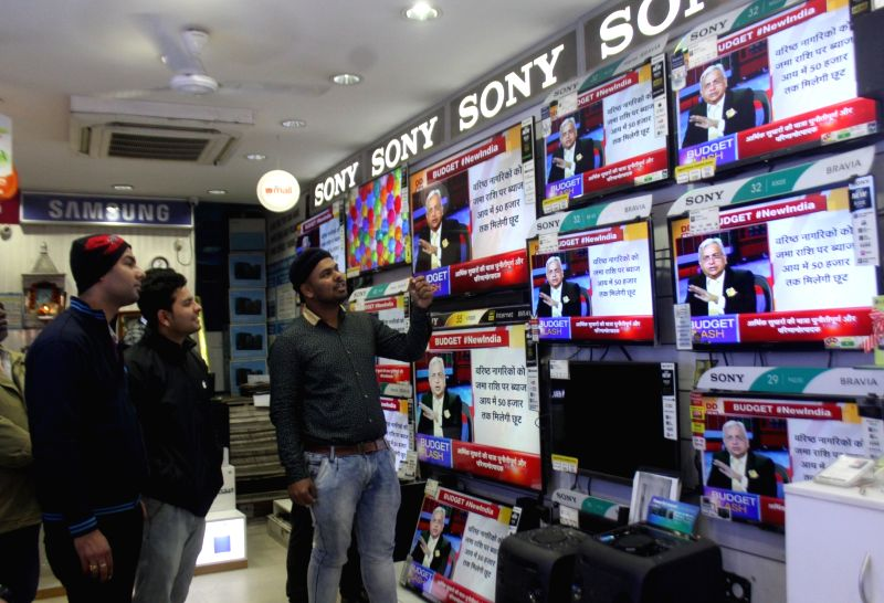 People watch the telecast of the Budget 2018-19 at a TV showroom in New Delhi on Feb 1, 2018.
