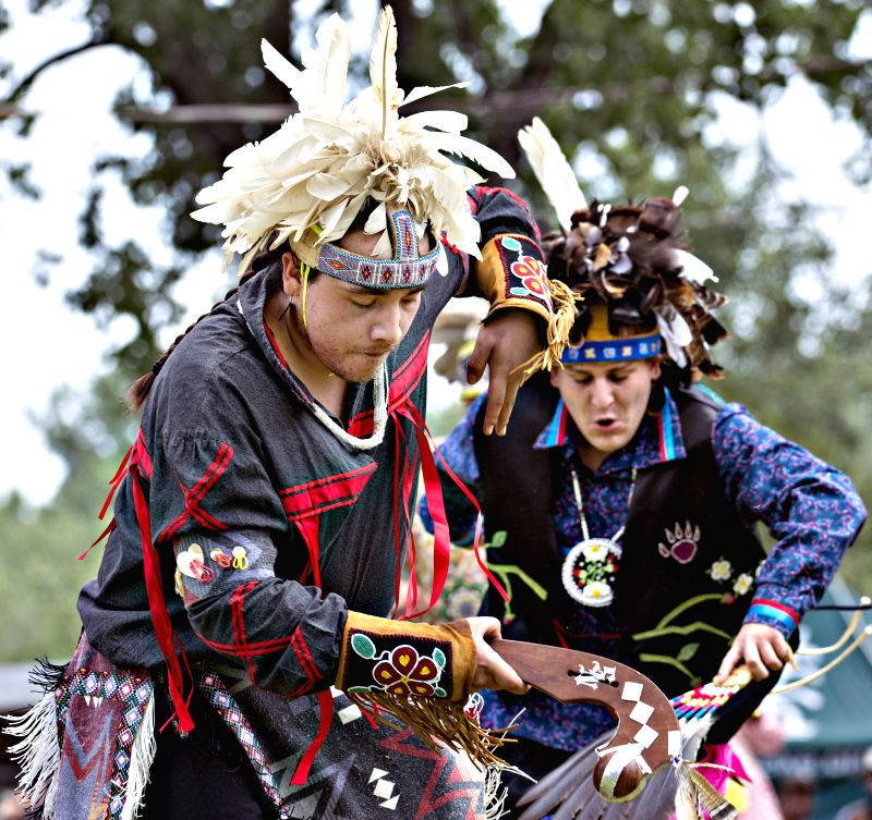 People wearing traditional costumes dance during the Echos of a Nation powwow at the Kahnawake reserve near Montreal, Canada, on July 11, 2015. The powwow is ...