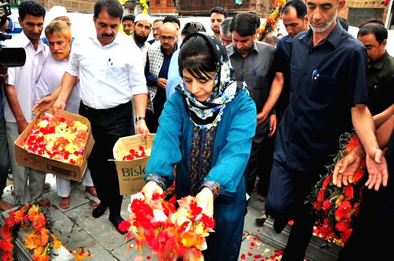 Peoples Democratic Party (PDP) President Mehbooba Mufti pays tribute at martyrs' graveyard in Srinagar on July 13, 2018. She said the BJP-led central government would end up creating more ... - Malik and Mehbooba Mufti