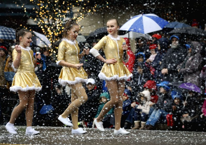 Performers walk along the street during the 12th Santa Claus parade in Vancouver, Canada, Dec. 6, 2015. Over 3,500 participants from more than 50 groups showcase ...