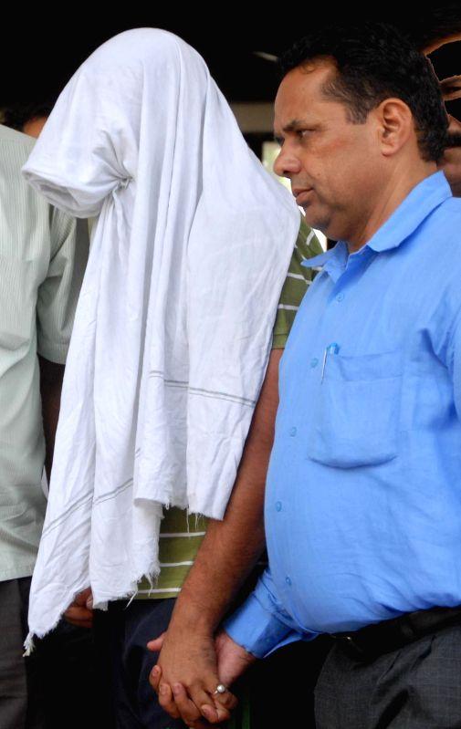 Personnel from Vigilance Bureau take away SHO Sandeep Kumar for taking bribe in Gurgaon on Aug 19, 2014. - Sandeep Kumar