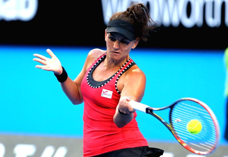 Australia's Casey Dellacqua returns a shot against Agnieszka Radwanska of Poland during their second session women's singles match on day one of the Hopman Cup tennis .