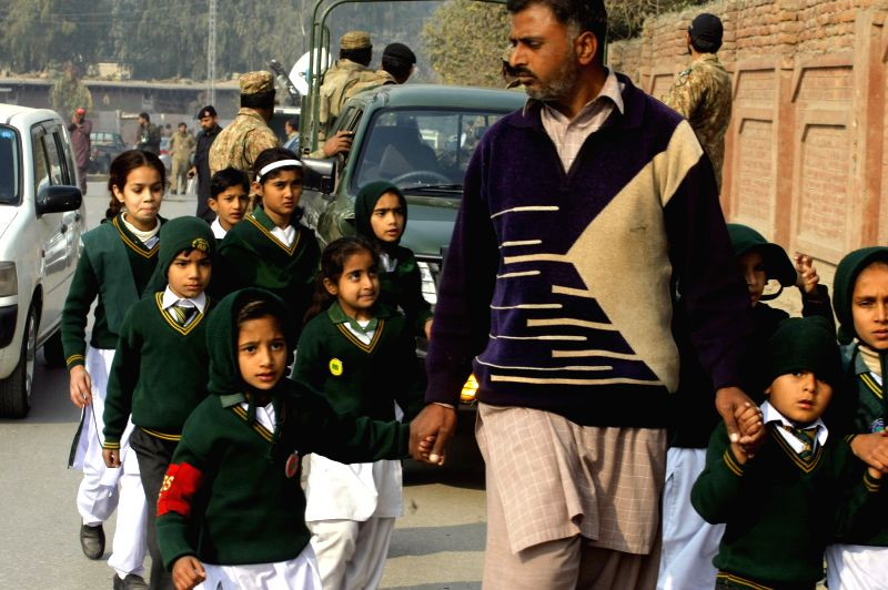 A man escorts school children after they were rescued from the school that is under attack by militant gunmen in northwest Pakistan's Peshawar, Dec. 16, 2014. At least 126 people had been ..