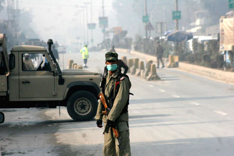A Pakistani army soldier stands guard near the attack site in northwest Pakistan's Peshawar on Dec. 16, 2014. At least 14 people including 12 children were killed and over 30 others injured