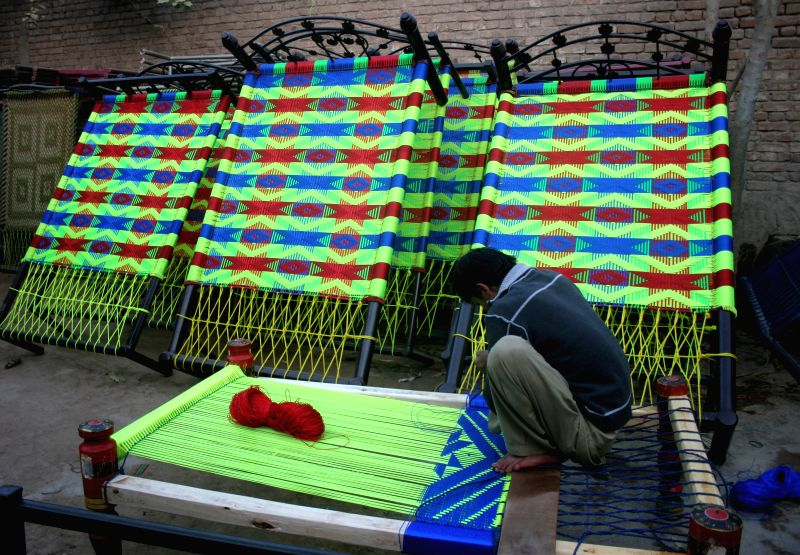A Pakistani man weaves a handmade traditional woven bed (charpai) in northwest Pakistan's Peshawar, Dec. 2, 2014. Charpai is a traditional woven bed widely used in villages in Pakistan. ...