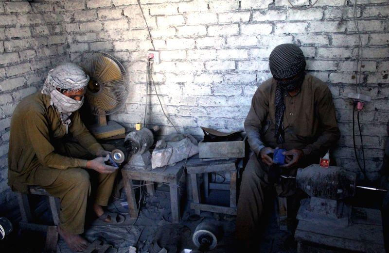 PESHAWAR, April 18, 2017 - Two men work with lapis lazuli stone at a factory in northwest Pakistan's Peshawar on April 17, 2017.