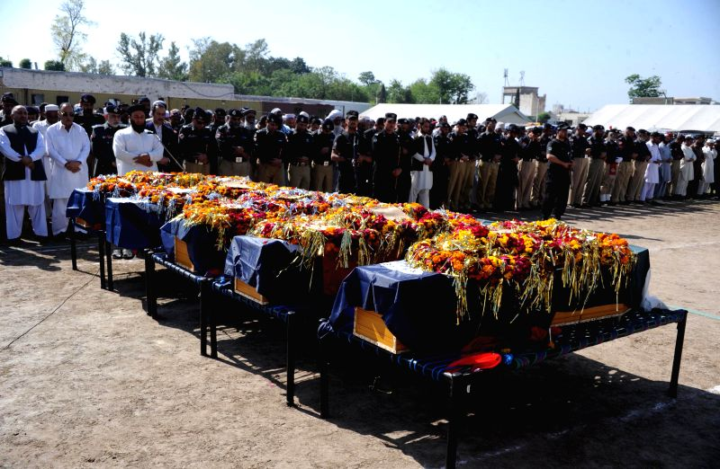 Pakistani policemen attend the funeral ceremony of their colleagues who were killed in an attack in northwest Pakistan's Peshawar, on April 22, 2014. At least ...