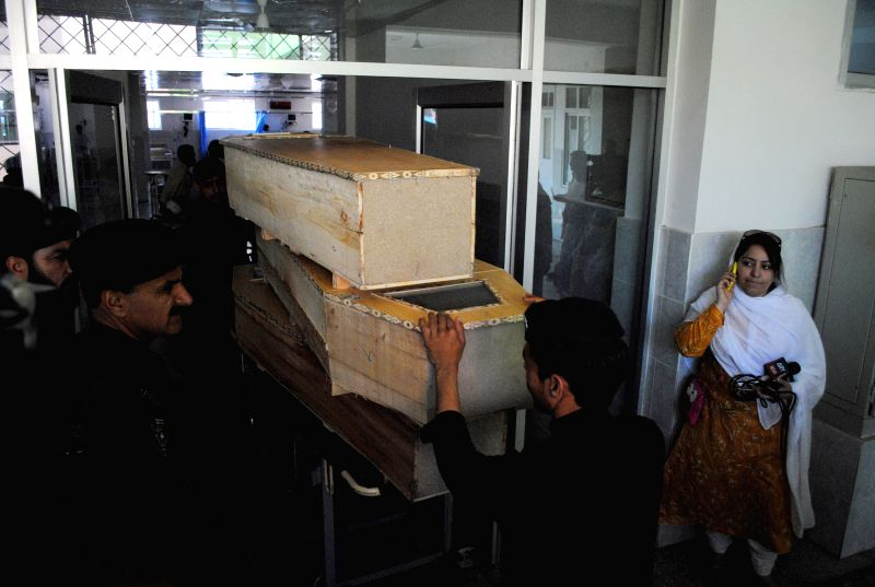 People transport coffins to a hospital in northwest Pakistan's Peshawar on April 22, 2014. At least four people were killed and 33 others injured when a bomb ...