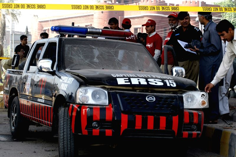 A damaged police vehicle is seen at the bomb blast site in northwest Pakistan's Peshawar on April 24, 2015. At least five policemen were injured when a bomb hit ...