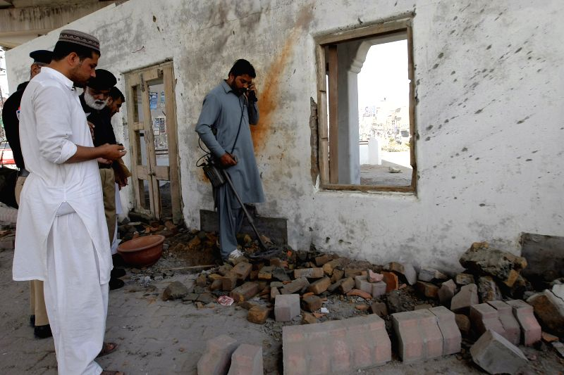 Policemen inspect the bomb blast site in northwest Pakistan's Peshawar on April 24, 2015. At least five policemen were injured when a bomb hit their vehicle in ...