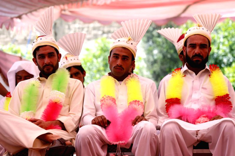 Pakistani grooms sit during a group wedding ceremony in northwest Pakistan's Peshawar on April 25, 2014. A total of 25 couples participated in a group wedding ...