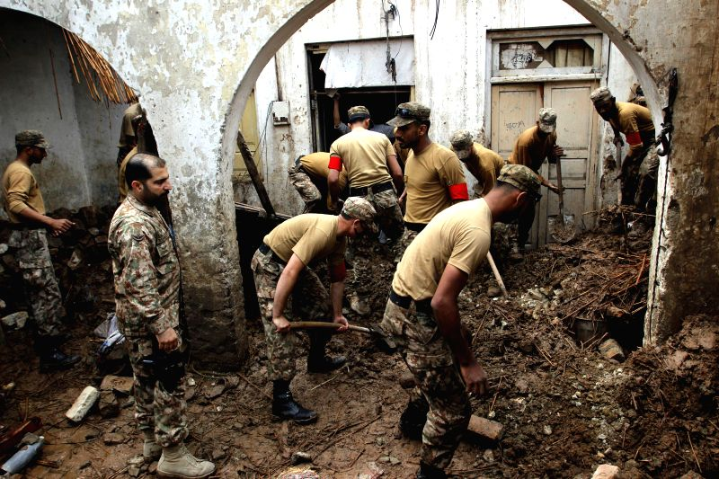 Pakistani soldiers remove belongings from a house after it was damaged in heavy rain and winds in northwest Pakistan's Peshawar, April 27, 2015. At least 30 ...