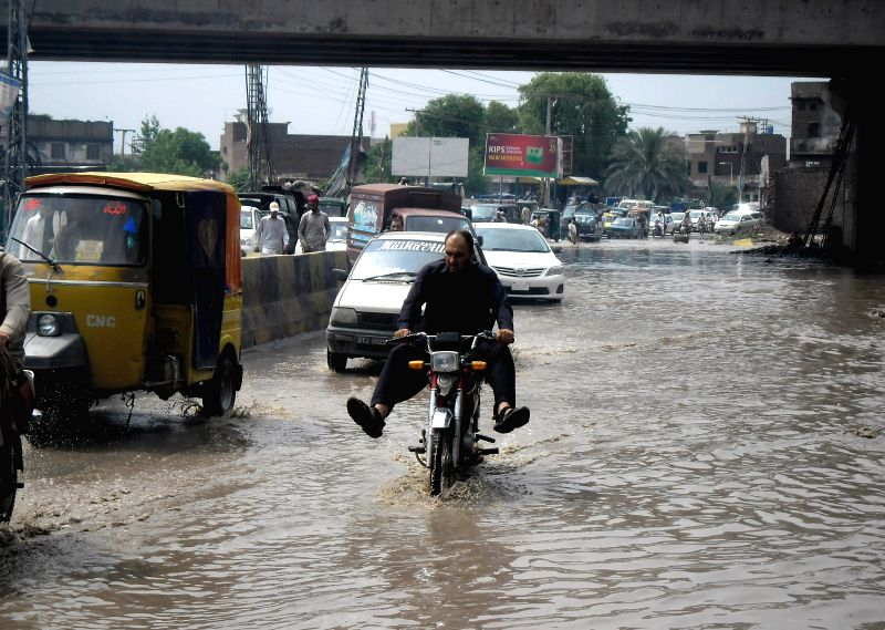 Vehicles move through flooded water after heavy rain in northwest Pakistan's Peshawar, April 30, 2015.