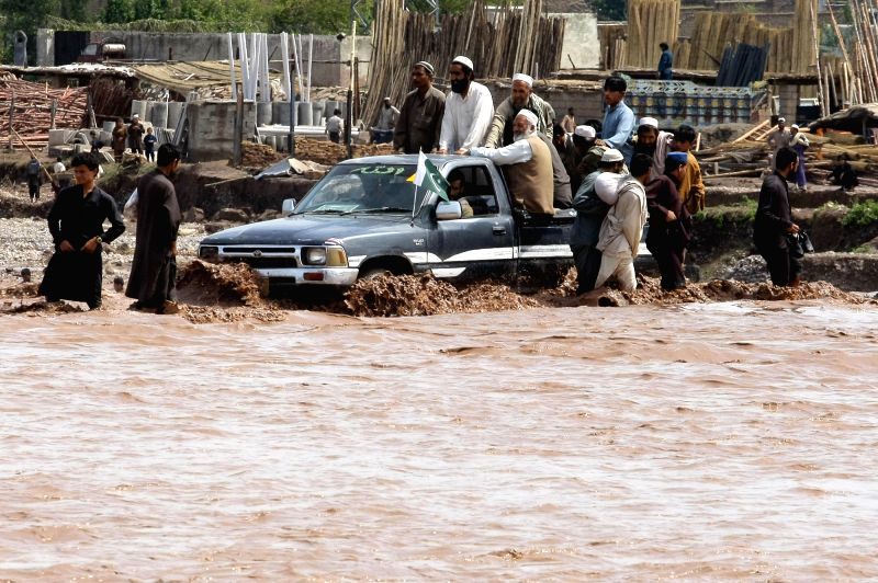 PESHAWAR, April 4, 2016 - A vehicle moves through a flooded street following heavy rain on the outskirts of northwest Pakistan's Peshawar, April 4, 2016. At least 65 people were killed and dozens of ...