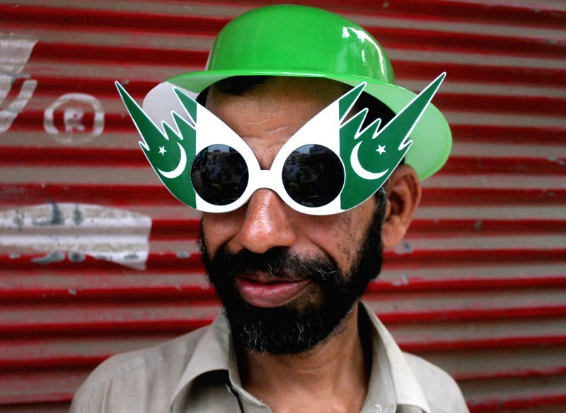A Pakistani man wears a glass decorated with elements from national flag on the eve of Pakistan's 68th Independence Day in Peshawar, northwest Pakistan, on Aug. ...