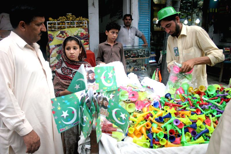 Pakistani people shop from a stall on the eve of Pakistan's 68th Independence Day in Peshawar, northwest Pakistan, on Aug. 13, 2014.   ..
