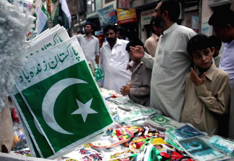 Pakistani people shop at a stall on the eve of Pakistan's 68th Independence Day in Peshawar, northwest Pakistan, on Aug. 13, 2014.